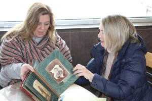 Cori Henderson shows antique album to Renee