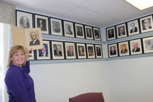 Executive Director Heather Richardson shows where the photo of Roy E. Warden will be placed as first president of the board of Arkansas State Board of Licensure for Professional Engineers and Surveyors